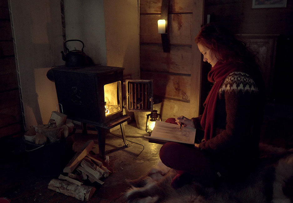 Linde Faas sketching next to a fire in cabin
