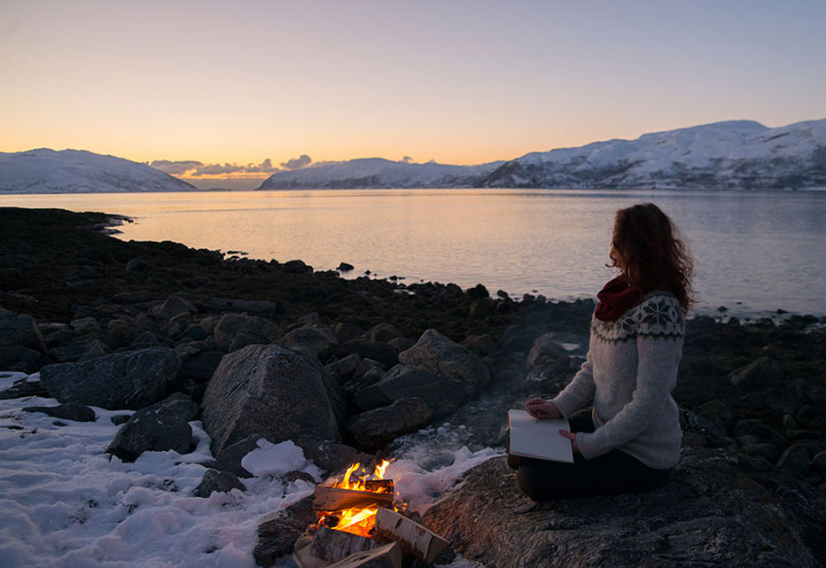 Linde Faas with a fire next to the fjord
